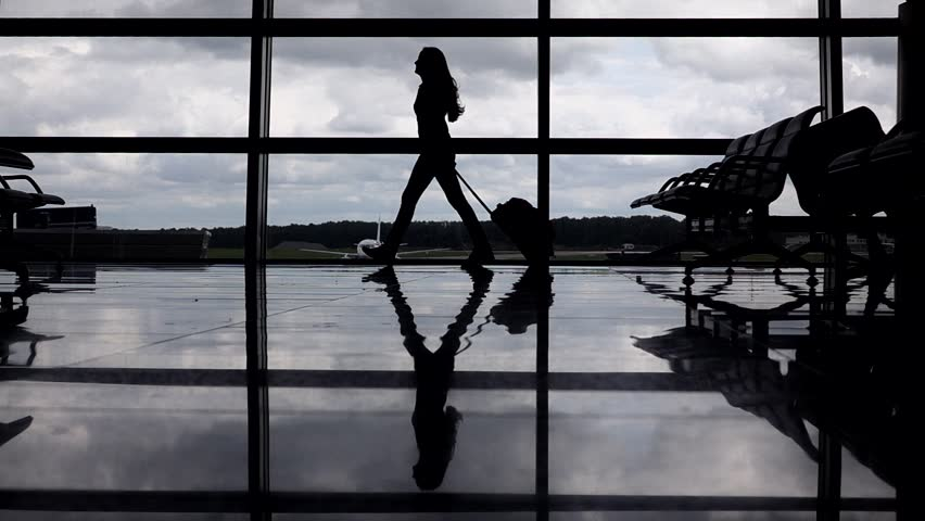 Lady silhouette slowly walk against large terminal window. Woman go with small rolling case in empty dark lounge, commercial airliner parked outside at airport apron field. Air transportation concept