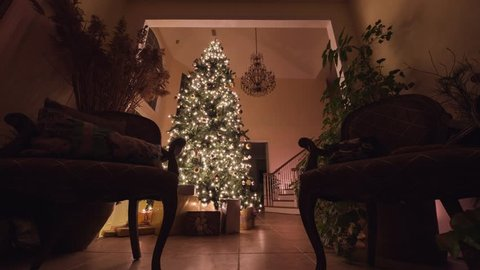 Big Christmas tree with glowing lights, ornaments, and presents in a beautifully decorated home. Dolly shot.