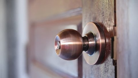 Men's hand opens and closes the brass door knobs