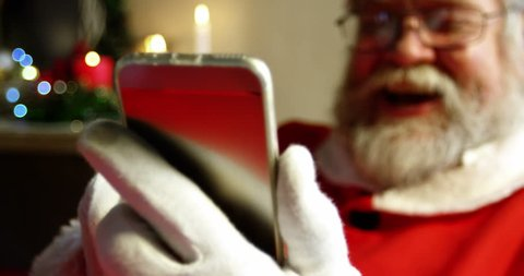 Santa claus using mobile phone during christmas time at home