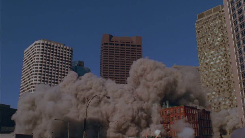 Day ND city skyline tall office buildings apartment building billowing smoke from lower floor 2 taller office buildings center implodes, billowing grey smoke blocking view implosion