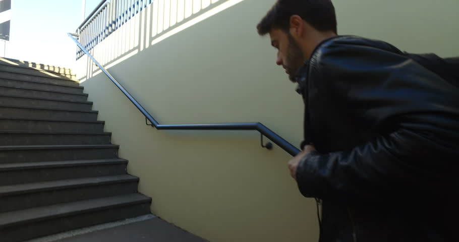 Boy University Student is climbing the stairs of the underground passage into a train station.