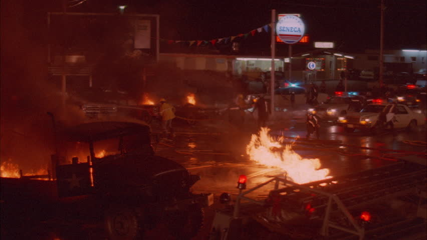 Night Pan over firemen working blazing fire, spot fires ground Police sheriffs holding back crowd background Gas station used car lot Burning military truck news footage, playback,