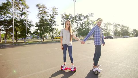 Modern young man and woman walking with Hover board. A new movement. Wide shot. Dual Wheel Self Balancing Electric Skateboard Smart