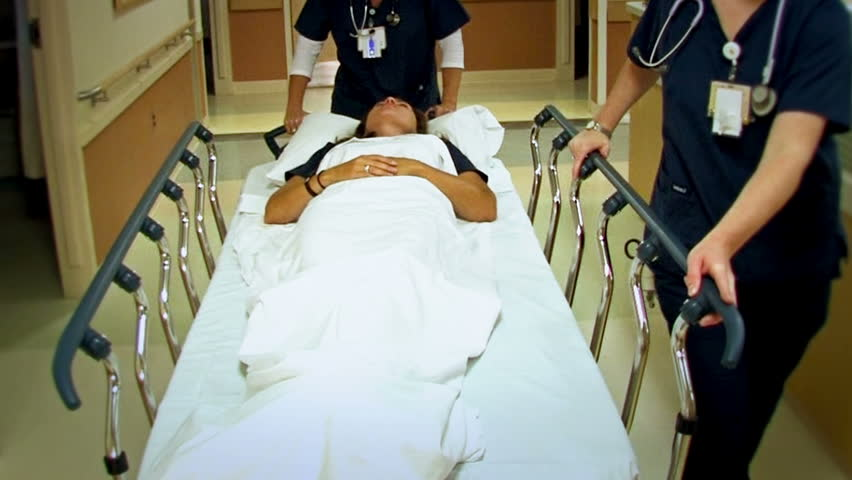 Woman patient on stretcher in a hospital's hallway.