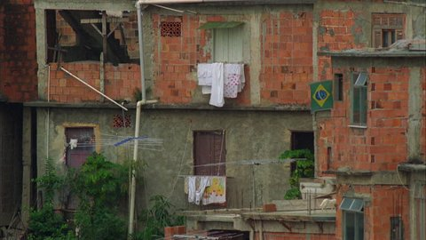 day rundown apartments foreign city slums shantytown favela, impoverished, underprivileged, poor, poverty with laundry hanging out windows Brazilian flag