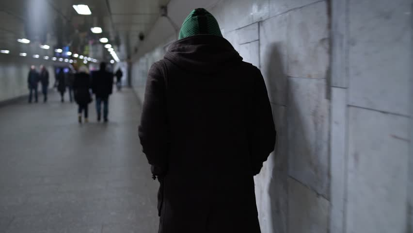 Suspicious hooded man goes through the underpass