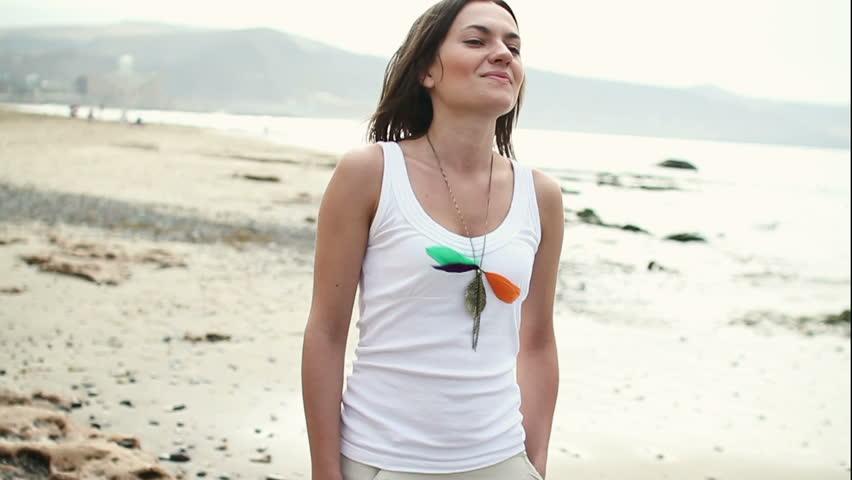 Happy woman walking on the beach, slow motion, steadicam shot