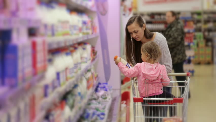 Attractive woman with cute little daugher picking fresh dairy products in refrigerated section in groceries. Mom and daugher choosing a milk in this scene. | Shutterstock HD Video #21407638