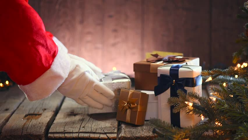 Santa Claus putting gifts under the Christmas tree with blinking garlands. Santa Claus giving gift box, holding a gift in his hands over wooden background.  Full HD 1080p video footage