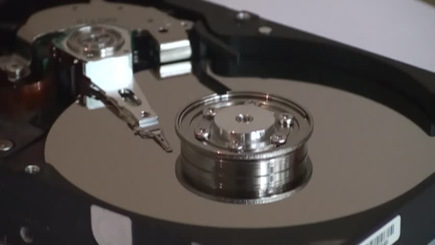Metal circle plate and magnetic head inside hard disk drive reading and writing data | Shutterstock HD Video #21495778