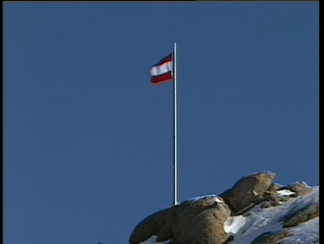The Austrian flag on top of a mountain