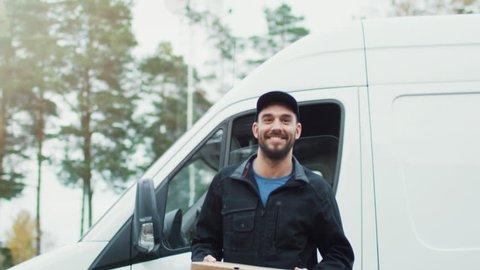 Smiling Pizza Delivery Guy Delivers Two Pizzas. Sunny Autumn with Yellow Birches and Pines is on the Background. Shot on RED Cinema Camera in 4K (UHD).