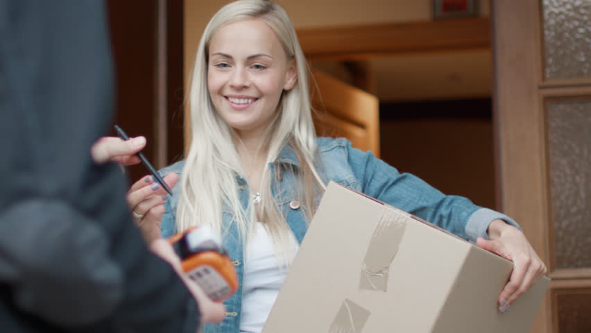 Smiling Woman Receives Postal Package after Signing Electronic Signature Device while Standing in the Open Doorway. Shot on RED Cinema Camera in 4K (UHD).