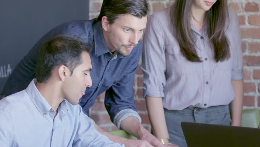 Group of young multiethnic millennial tech workers in a creative start up work environment holding a project meeting around a computer in a conference room | Shutterstock HD Video #21548098