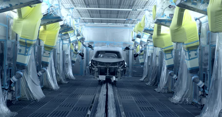 Robots are painting cars in production line in automobile factory
