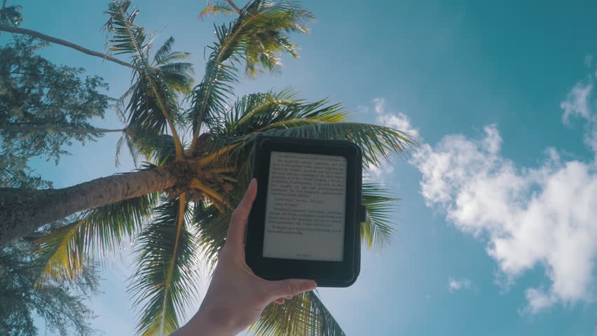 Woman's hand holding a book reader with a palm tree in the background | Shutterstock HD Video #21567181