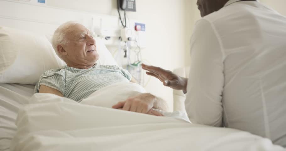 4K Friendly doctor comforting elderly patient at his bedside (UK-Oct 2016)