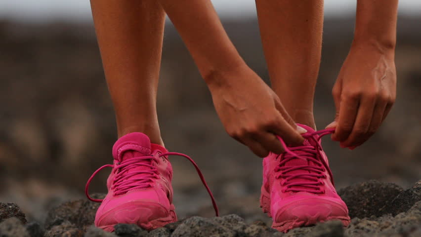Running woman tying shoe laces going running - girl trail runner. Closeup of female legs and running shoes in action. Girl athlete fitness runner running fast outside in trail running shoes. 59.94 FPS