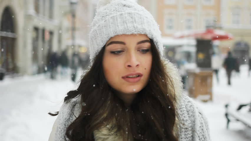 Attractive beautiful lady walking over snowy city background