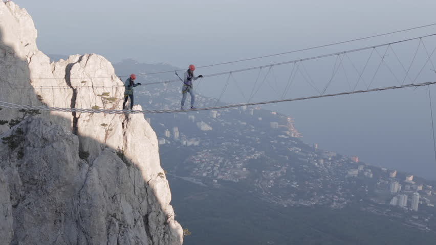 Two Girl Walking Along a Rope Bridge Over the Precipice at High Altitude