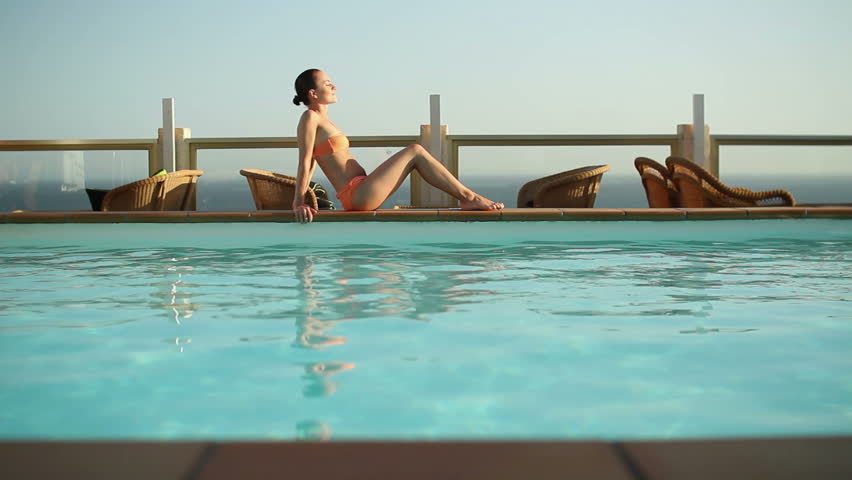 Happy young woman relaxing by the luxury swimming pool