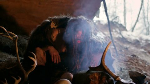 Phrehistoric cave man makes first fire, blows on it in his cave on the background of bones and skulls. Snow winter outside