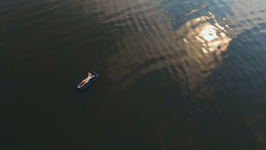 Young Girl Floats On An Inflatable Mattress In The Lake.Aerial View:Girl Is  Happy And Float On Inflatable Mattress.Beautiful Girl Floating On Inflatable  ...