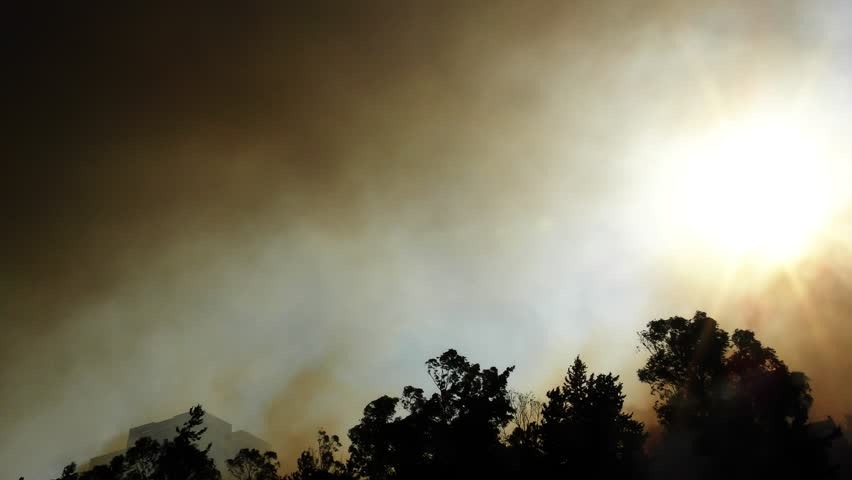 An airplane drops red fire retardant on forest fire.