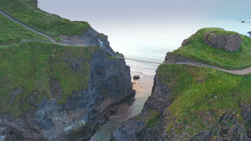 The rope bridge connecting the two cliffs in Northern Ireland it is called the Carrick-a-Rede Rope Bridge taken in an aerial shot