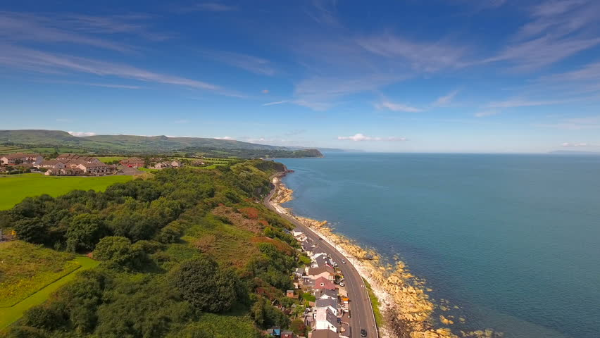 Aerial landscape shot of the coastal village of Cushendun found in the Northern Ireland with the big sea and the trees in the forest