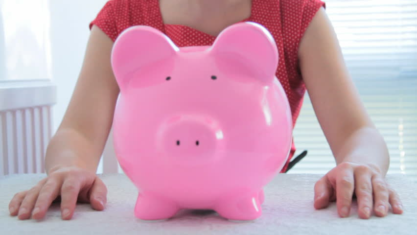 Female checking savings in piggy bank and looking disappointed