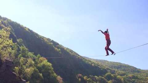 Young Man Balancing On Slack-Line Over Mountains During Autumn Extreme Sport Walking Adventure Danger Sunny Slacklining Brave Happy Hiker Safety Tree Sky