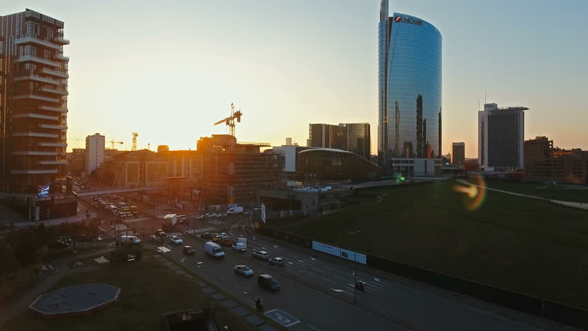 City Sunset over Milan, aerial footage, amazing flight over new Porta Nuova financial district and Porta Garibaldi train station with a road intersection with cars