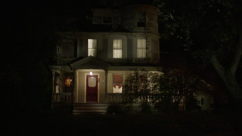 night beige wood clapboard house , wrap around porch, dormers, turret, bay windows, some lights on, screened red door, autumn, fall trees, see guest house r background , (Oct 2012)