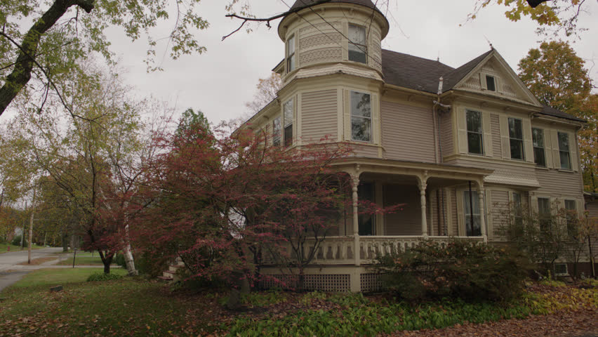 day then pan right along right corner side beige wood clapboard house , wrap around porch, bay windows, turret, dormers, detached garage, back porch, autumn, fall trees, (Oct 2012)