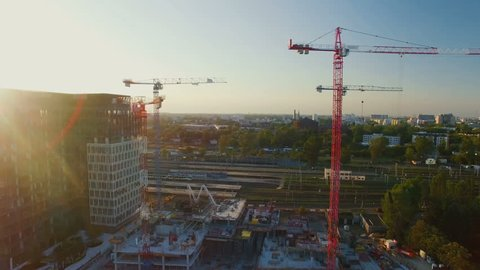 Aerial Shot of Cranes on a Construction Site. Great Cityscape is Visible in Sunlight. Shot on Phantom 4K UHD Camera.