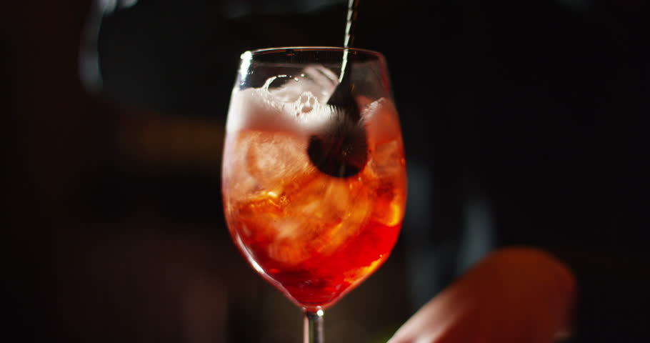 in a nightclub or pub, a professional bartender preparing a cocktail with ice a mix of alcohol. The barman measure quantities for a perfect cocktail. concept: disco, fun, friends, cocktail.