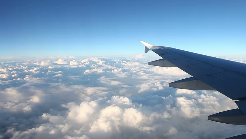 View of clouds through window of an airplane on a sunny day.  Full high definition video 1920X1080.