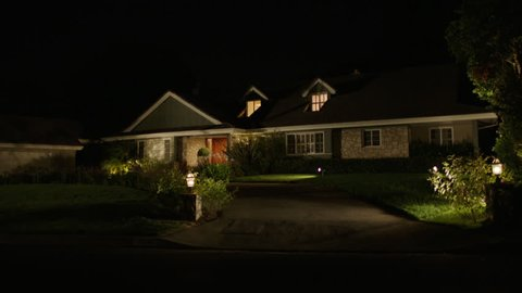 night one story house 2 dormer windows that can play two story house Nice landscaping No interior lights on, then one upstairs light turns on, then light turns then back