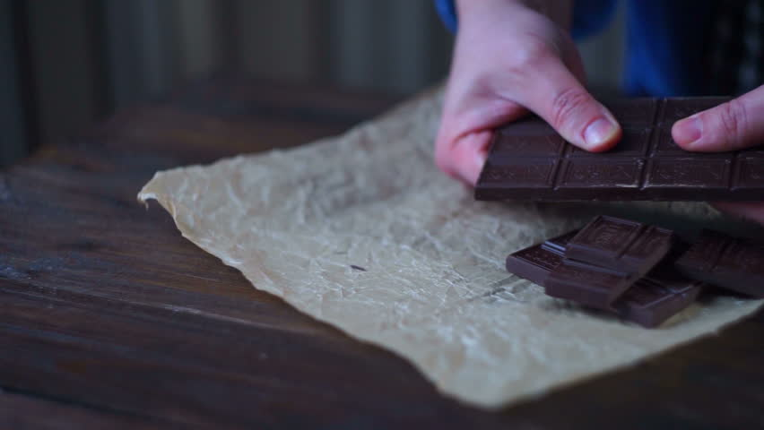 Man hands breaking dark chocolate. Dark chocolate bar. Chocolate pieces on cooking paper. Sweet ingredient for cooking cake
