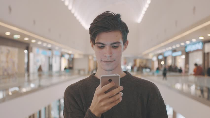 Young men using smartphone at shopping mall. Portrait | Shutterstock HD Video #21865699