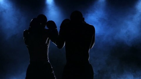Coaching two male boxers filmed in slow motion and silhouette