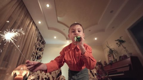 Little boy in Birthday cap holding sparkler and blowing whistle at camera in modern room.
