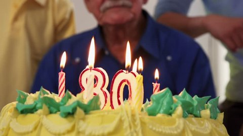 Group of old friends and family celebrating senior man birthday in retirement home. Happy elderly people having fun during party. Grandfather blowing candles on cake and smiling in hospice