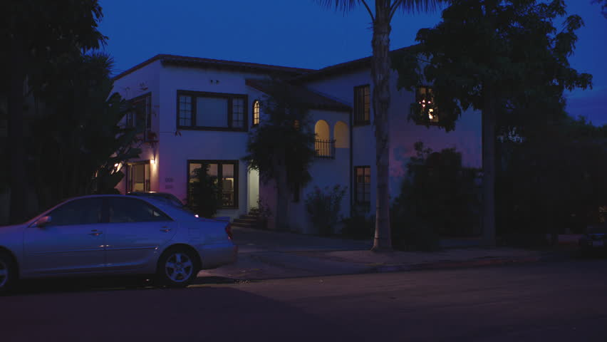 Magic Hour Small 2 Story Stucco Spanish Style Apartment Duplex Brown Trim Tiled Roof Palm Lights On Car Out Driveway