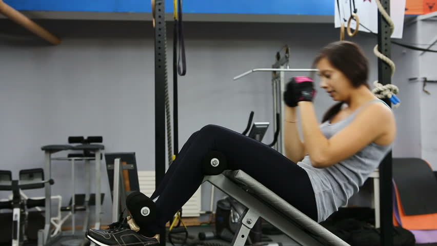 Woman practicing sit-ups on exercise machines at the gym. Woman exercise sit-ups on the weight bench | Shutterstock HD Video #21974128