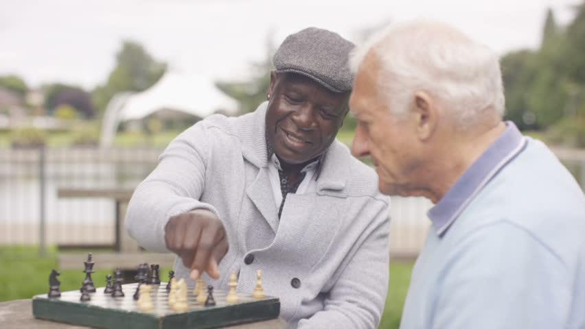 4K Happy senior male friends relaxing in the park playing chess (UK-Oct 2016)