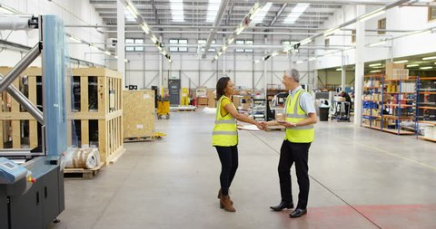 4K Business managers having a discussion in factory warehouse, with workers busy in the background. Slow motion.