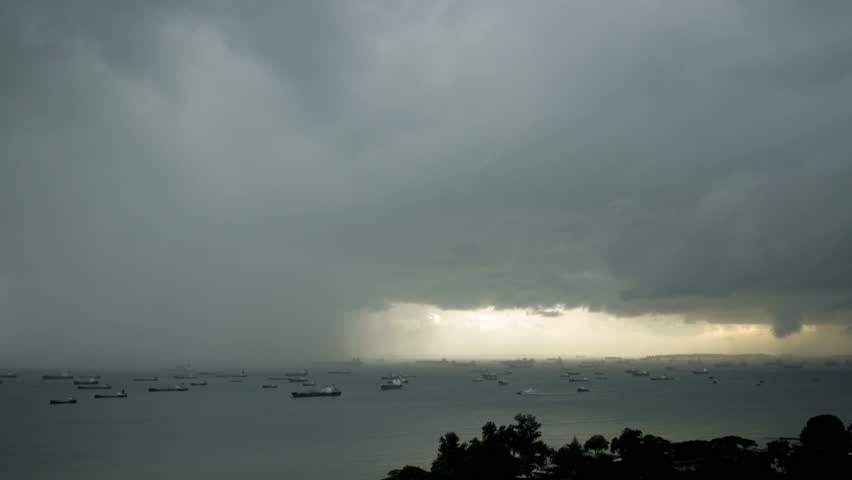 Landscape over South China Sea with docked ships, with passing rain clouds in distance during sunset.